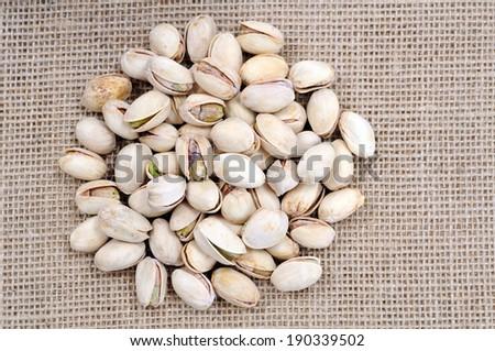 group of salty pistachio on burlap background - stock photo