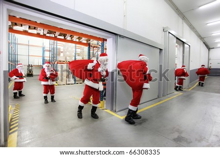 group of santa clauses leaving a gift distribution center with red sacks - stock photo
