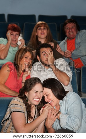Group of scared people watch horror movie in theater - stock photo
