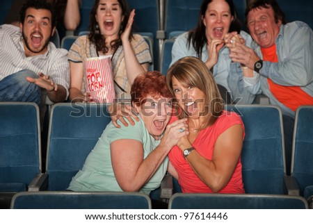 Group of scared people watching movie in theater - stock photo