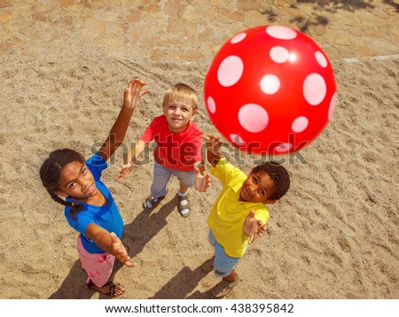 Group of school aged kids playing with a ball outside - stock photo