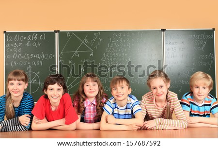 Group of school children studying in classroom.