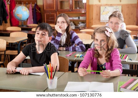 Group of schoolchildren at classroom during a lesson - stock photo