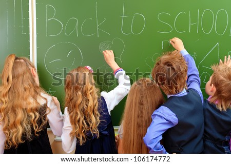 Group of schoolchildren writing on a blackboard at a classroom. Education. - stock photo
