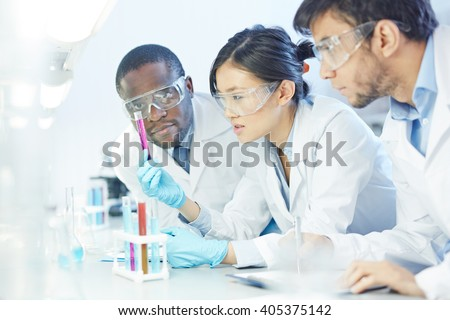 Group of scientists studying reaction of some chemical - stock photo