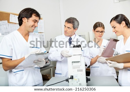 Group of scientists working together in medical laboratory - stock photo