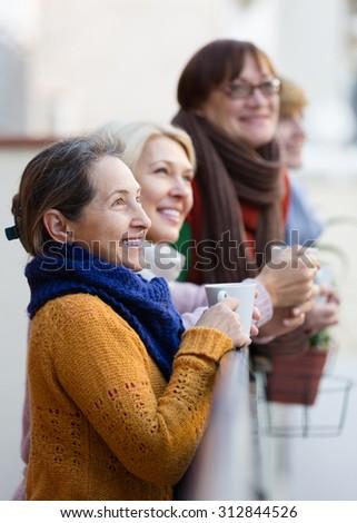 Group of senior female friends drinking tea at balcony - stock photo