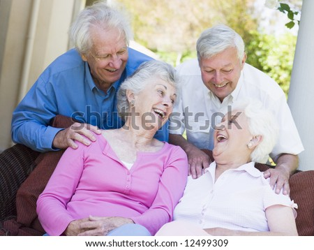 Group of senior friends sitting on garden seat laughing - stock photo