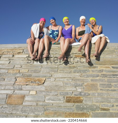 Group of senior women in bathing suits sitting on stone wall - stock photo