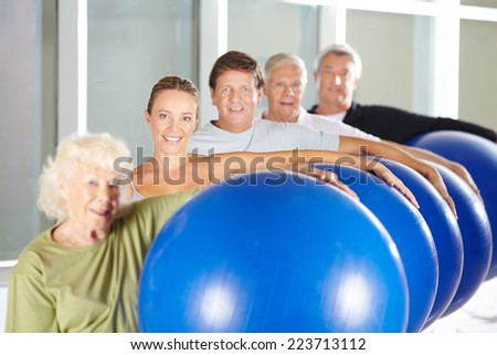 Group of seniors doing fitness training with gym balls in rehab center - stock photo
