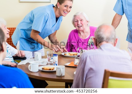 Group of seniors having food in nursing home, a nurse is serving - stock photo