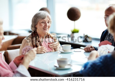 Group of seniors meeting every week in cafe to play cards - stock photo
