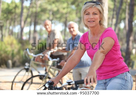 group of seniors riding bikes in the park - stock photo