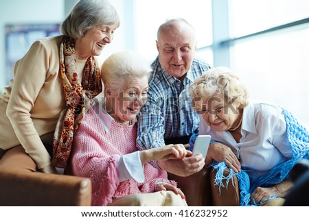 Group of seniors using mobile phone - stock photo