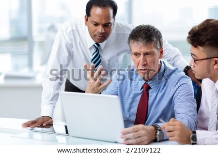 Group of serious business people discussing information on the laptop - stock photo