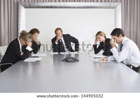Group of serious business people on conference call in boardroom - stock photo