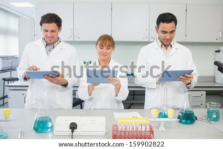 Group of serious scientists using tablet PCs in the laboratory - stock photo