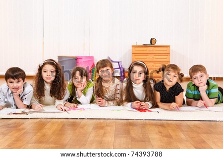 Group of seven junior school students lying in line - stock photo