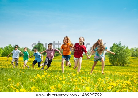 Group of seven running in the park kids, boys and girls, black and Caucasian - stock photo