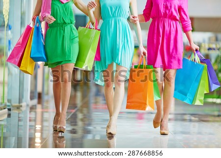 Group of shoppers in bright dresses walking in the mall - stock photo