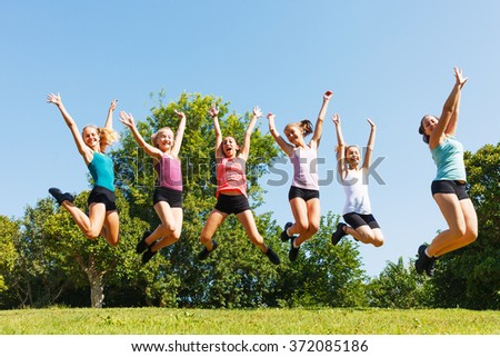 Group of six happy children jumping on meadow.