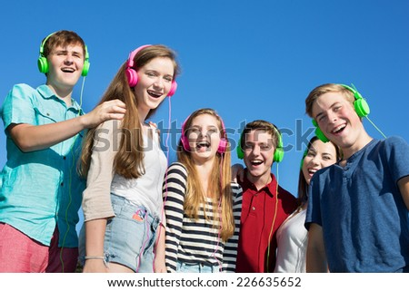 Group of six happy teenagers laughing outdoors