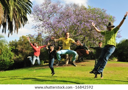 Group of six silly adults jump into the air with joyful enthusiasm