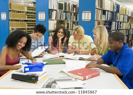 Group of six students working around table in library - stock photo