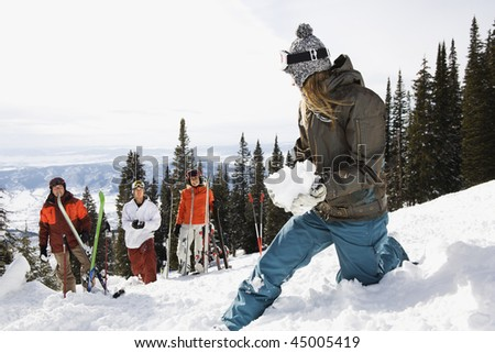 Group of skiers standing on Colorado slope watching another make a snowball. Horizontal shot. - stock photo