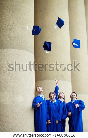 Group of smart students in graduation gowns throwing their hats - stock photo