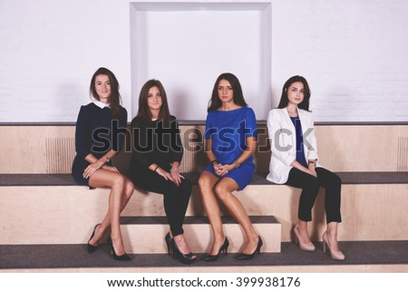 Group of smarts female office workers dressed in formal wear are resting after conference with boss. Young attractive women are posing in modern interior after lectures in economics at Business School - stock photo