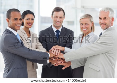 Group of smiling business people piling up their hands together in the workplace - stock photo