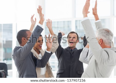 Group of smiling business people raising their hands in the workplace - stock photo