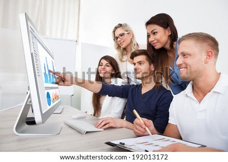 Group of smiling businesspeople using desktop PC together in office - stock photo