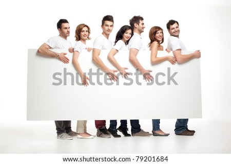group of smiling friends holding white banner - stock photo