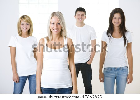 Group of smiling friends standing and looking at camera. They have on white t-shirt. Front view. - stock photo