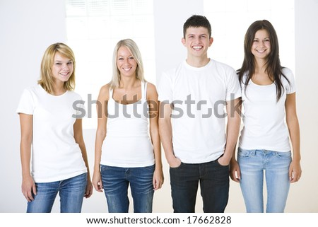 Group of smiling friends standing and looking at camera. Theyl have on white t-shirt. Front view. - stock photo