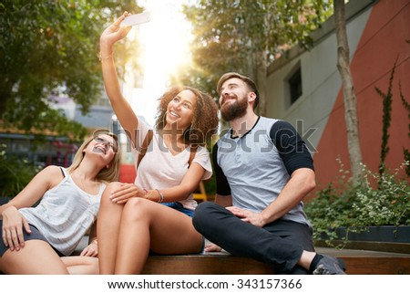 Group of smiling friends taking selfie with smart phone. Multiracial man and women enjoying themselves outdoors and taking pictures with mobile phone. - stock photo