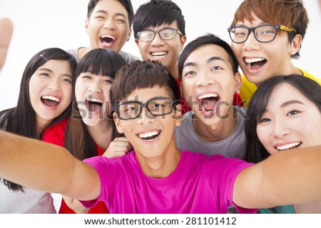 group of smiling friends with camera  taking self photo - stock photo