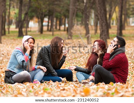 Group of smiling friends with smartphones in autumn park - stock photo