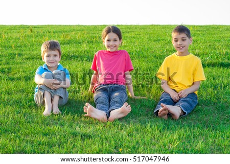 Group of smiling kids sitting on the green grass meadow