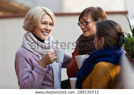 Group of smiling mature women drinking tea at balcony - stock photo