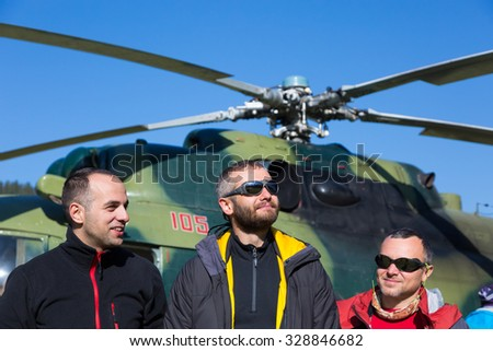 Group of Smiling Mountain Climbers Arrived to Exotic Destination by Helicopter Sporty Clothing Jacket Sunglasses - stock photo