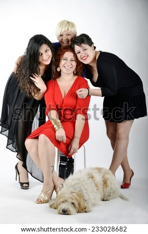 Group of smiling multiethnic adult women friends with different hair colors in elegant clothes with a lying dog (spinone italiano). Isolated on white background. - stock photo