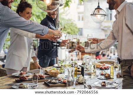 Group of smiling people cheering with wine and rising glasses on celebration at restaurant.