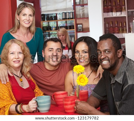 Group of 5 smiling people in a coffeehouse - stock photo