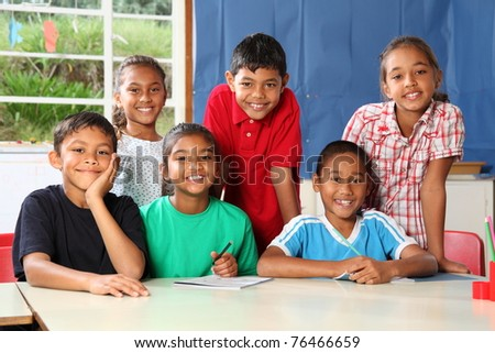 Group of smiling school children at classroom desk