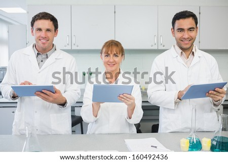 Group of smiling scientists using tablet PCs in the laboratory - stock photo