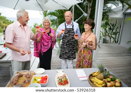 Group of smiling seniors with a glass of wine in front of a table - stock photo