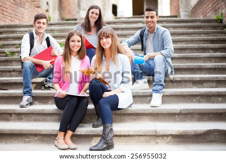 Group of smiling students sitting on a staircase - stock photo